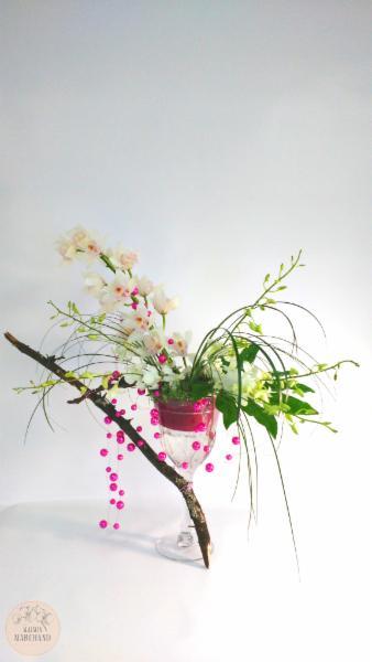 -Le Féminin:     ce bouquet de fleurs est composé de cymbidium blancs et roses, de dendrobium blancs, de bear grass, d'aralias et de perles. - Maison Marchand Fleuriste