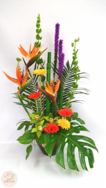 -L'Amazone:     Ce bouquet de fleurs est composé de mollucellas, d'oiseaux du paradis, de liatris violet, de gerberas jaunes et oranges, de cymbidius, de feuilles de monteras et de bambous.