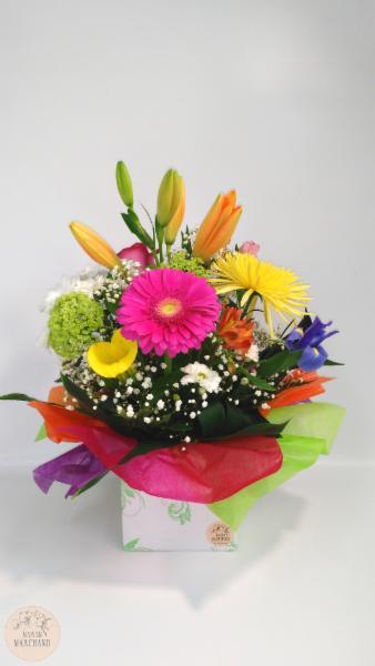 Boîte à fleurs:     ce bouquet de fleurs est composé de gerberas fushia, de lys orientales oranges, de roses, d'alstomerias oranges et roses, de fujis jaunes, d'iris bleus, de marguerites de Hollande blanches, de mirabellas blanches et d'hydrangés verts