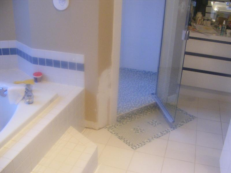 Bathroom renovation, with unusual detailing on the floor. The tile bathmat effect at the entrance of the shower is unique. Modern simple style, this rebuilt bathroom and shower is in Victoria, BC .