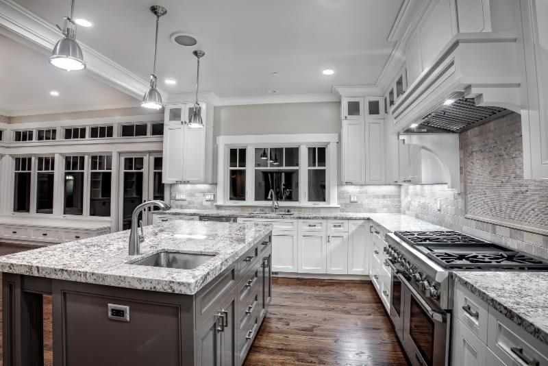 This amazing renovation combined the light coloured  3x6 classic stone subways & granite counters with the deep warm tones of a hickory hardwood. Just enough to warm you up! (Cochrane Floors & More)